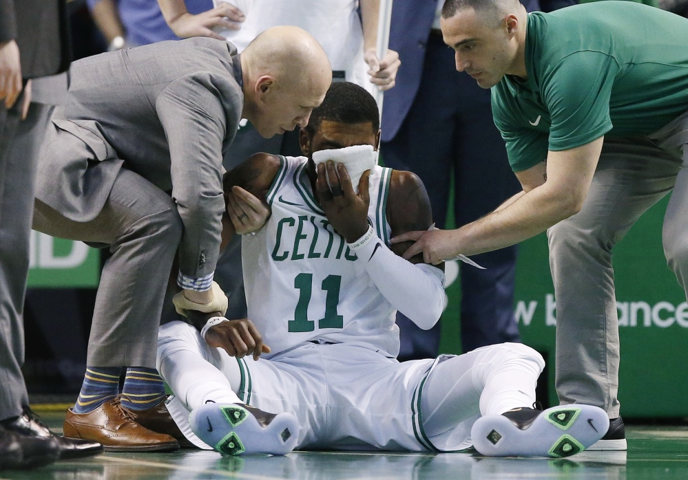Team personnel assist Boston's Kyrie Irving after he was injured in the first quarter Friday night against the Charlotte Hornets in Boston. Irving took an elbow to the face and left the game.