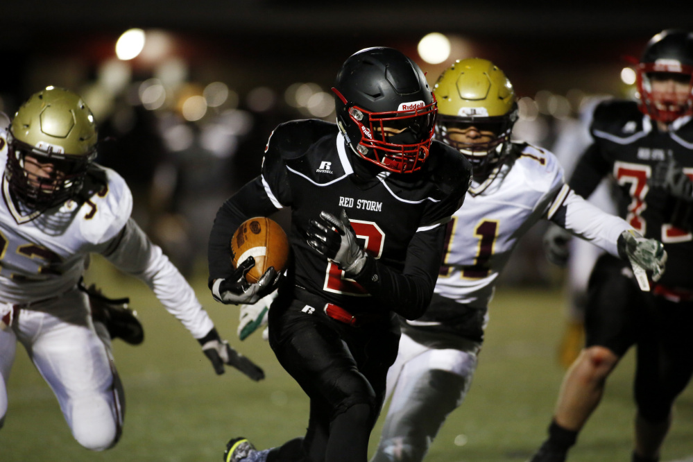 Scarborough's Jarett Flaker carries the ball as Thornton Academy's Thomas Palmer, left, and C.J. LaBreck try to tackle him Friday night during the Class A South championship game at Scarborough High.