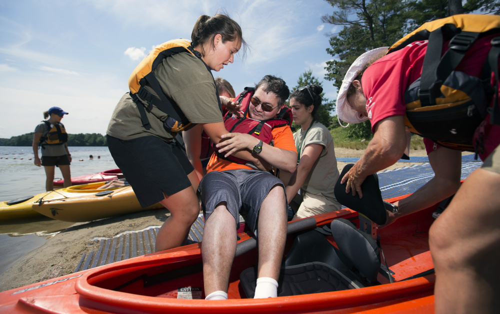 Johnny Nguyen is lowered into a tandem kayak by staff members of Massachusetts' Universal Access Program during an event at Cochituate State Park in Natick, Mass., last summer. The commonwealth offers adaptive recreational opportunities to people with physical disabilities and serves as a model for other states.