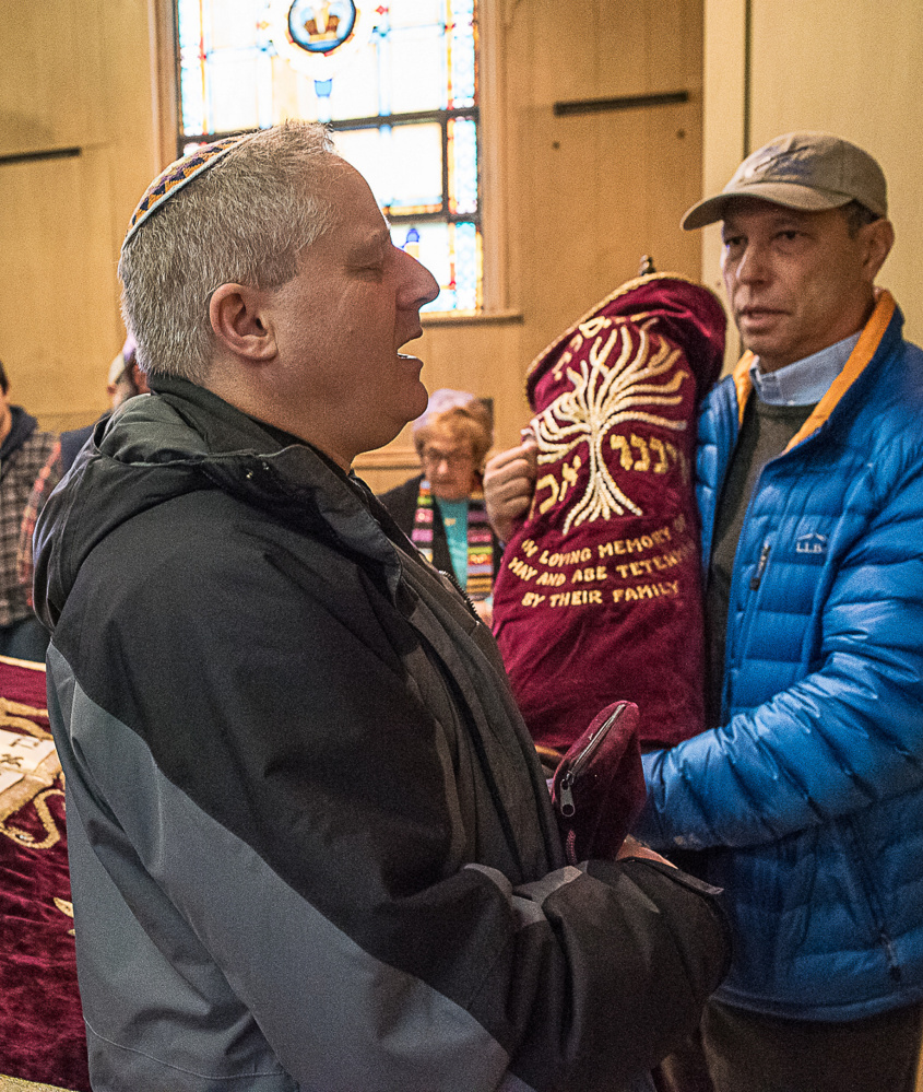 Rabbi Sruli Dresdner and Jamie Isaacson perform the deconsecration at Beth Abraham Synagogue in Auburn Sunday. The Torah, held by Isaacson, right, moved to Temple Shalom.