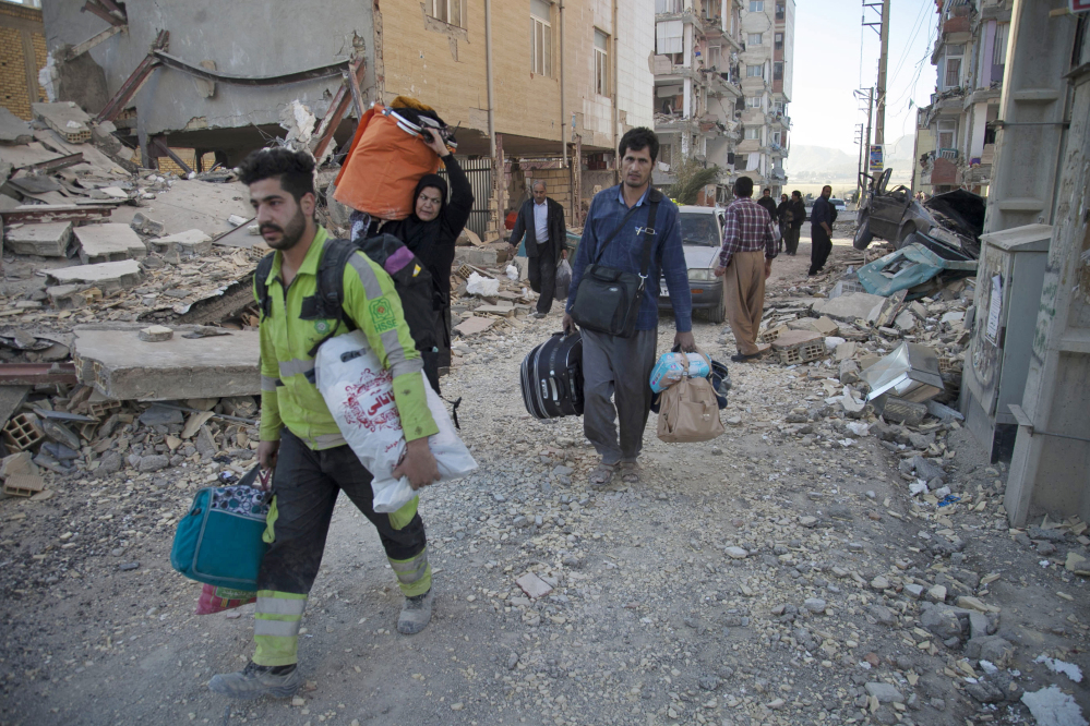People carry their belongings in Sarpol-e-Zahab, western Iran after a powerful 7.3 magnitude earthquake struck the Iraq-Iran border region on Monday and killed more than 300 people in both countries.