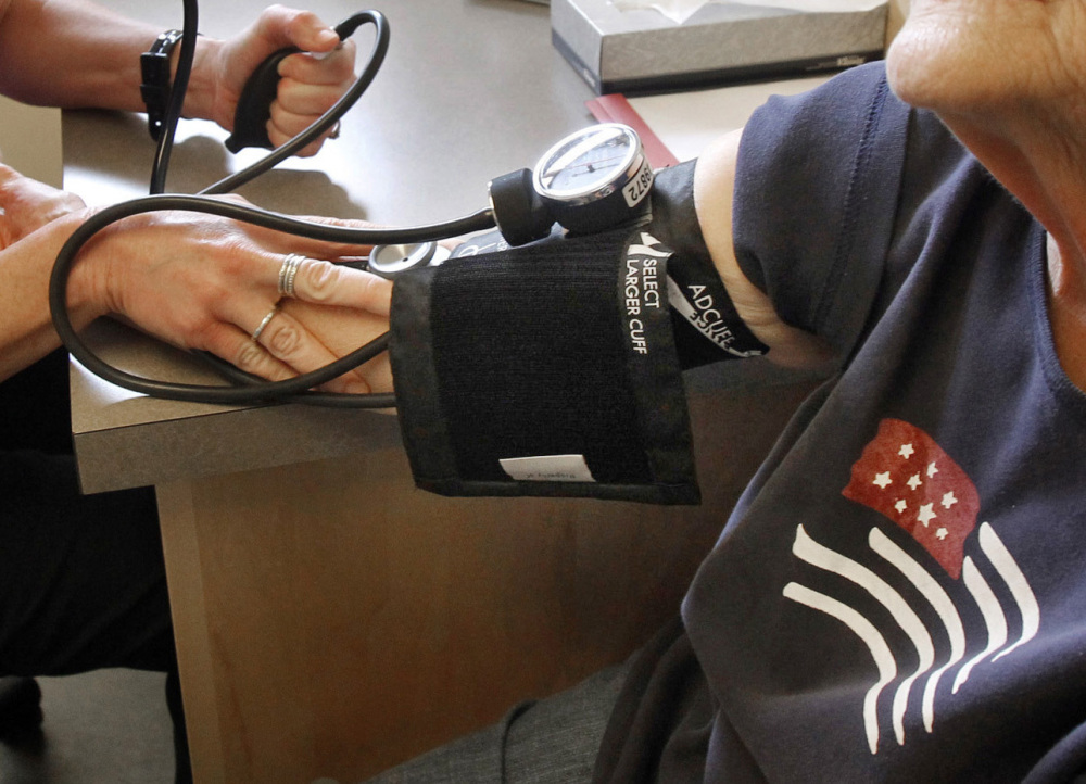 A patient has her blood pressure checked by a registered nurse in Plainfield, Vermont. New medical guidelines announced Monday lower the threshold for high blood pressure, adding 30 million Americans to those who have the condition.