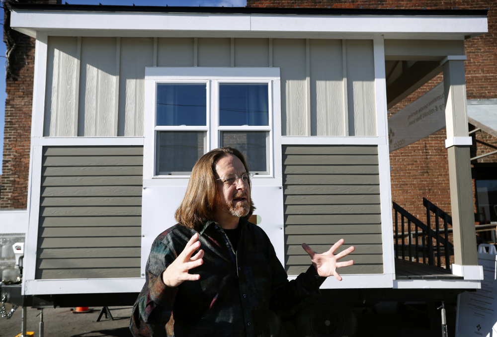 Joe Stevens stands in front of one of the tiny homes his student group built in hopes of helping the homeless in Des Moines, Iowa.