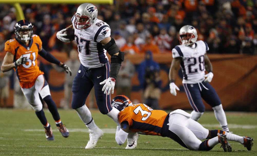 Patriots tight end Rob Gronkowski is hit by Broncos strong safety Justin Simmons during the second half of their game in Denver last Sunday. Gronkowski is likely to be covered by Raiders safety Obi Melifonwu, a second-round pick, on Sunday.