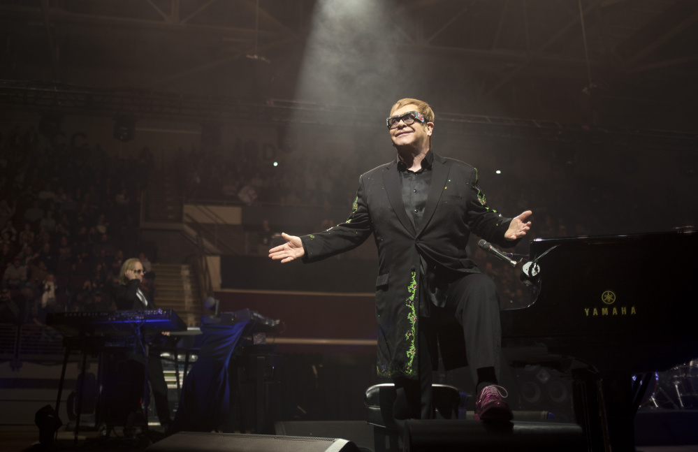Elton John hops off the piano and gestures toward the excited crowd during his first song at the Cross Insurance Arena on Friday night.