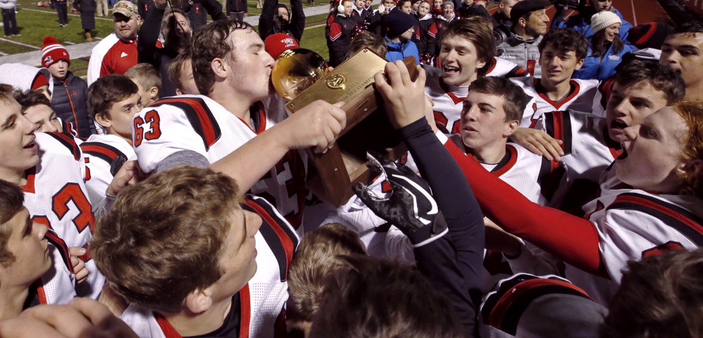 Evan Leach kisses the Class D state championship trophy after Wells defeated Foxcroft Academy 48-0 on Saturday afternoon at Fitzpatrick Stadium, completing a 12-0 season.