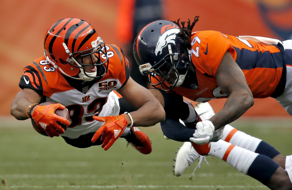Bengals receiver Tyler Boyd lunges forward while being tackled by Denver's Bradley Roby. Cincinnati dealt the Broncos their sixth straight loss, 20-17.