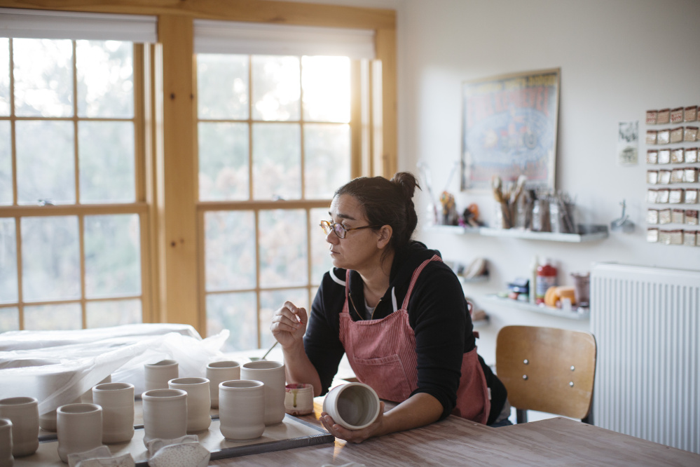 Ayumi Horie glazes new work in her studio in Portland. Horie is a ceramics artist who often uses her art to make statements and create dialogue about social and political issues.