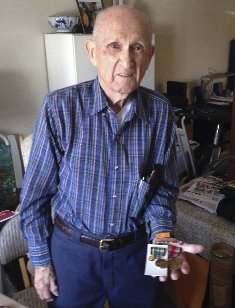 In this Tuesday, Nov. 21, 2017, photo, World War II veteran Kenneth F. Lincoln, 90, displays at his North Attleborough, Mass., home some of the medals he earned while serving in the U.S. Navy. Lincoln is finally getting the military decoration he earned for fighting a large fire that broke out among straw huts in Rabat, Morocco in the summer of 1946. He will receive a Moroccan award for meritorious conduct on Sunday, Nov. 26 in North Attleborough. (AP Photo/ Jennifer McDermott)