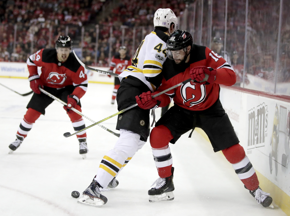 Bruins defenseman Rob O'Gara and New Jersey's Drew Stafford battle for the puck near the boards in the second period Wednesday night.
