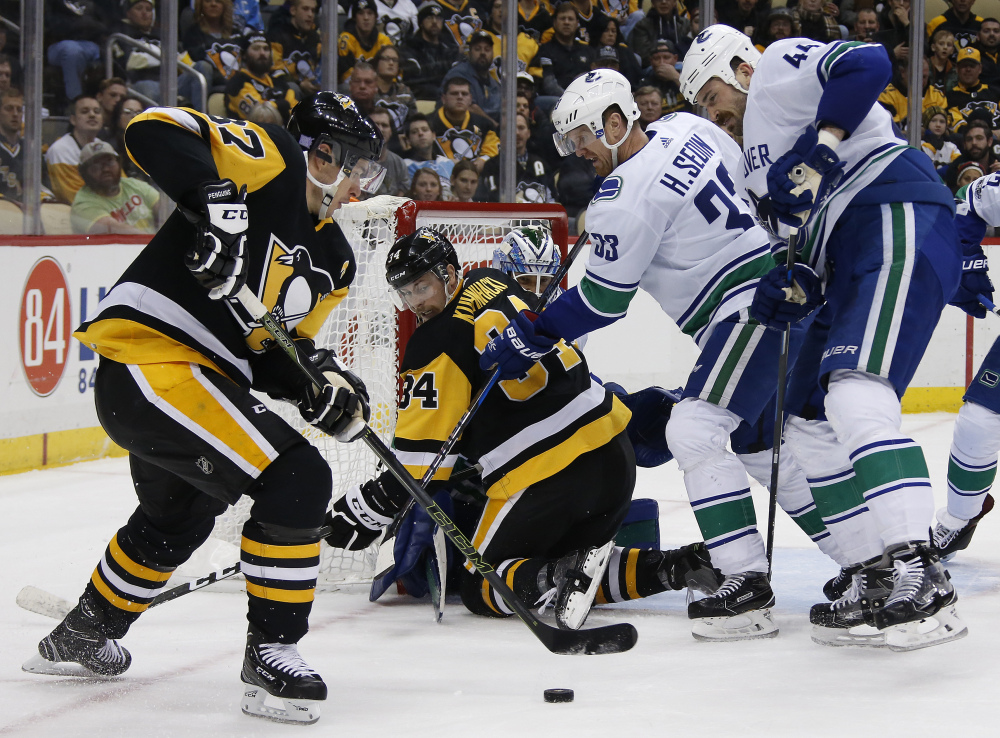 Pittsburgh's Sidney Crosby looks for an opening in a crowded crease during the second period Wednesday night against visiting Vancouver.