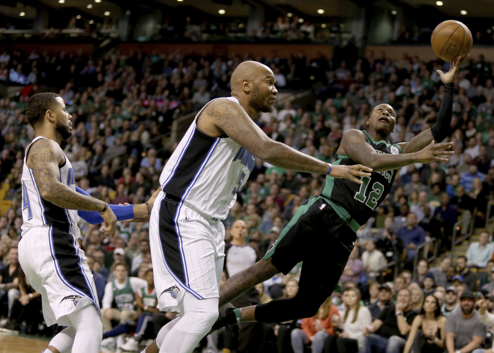 Boston's Terry Rozier drives to the basket ahead of Orlando's Marreese Speights, center, and D.J. Augustin, left, during the first half Friday night in Boston.