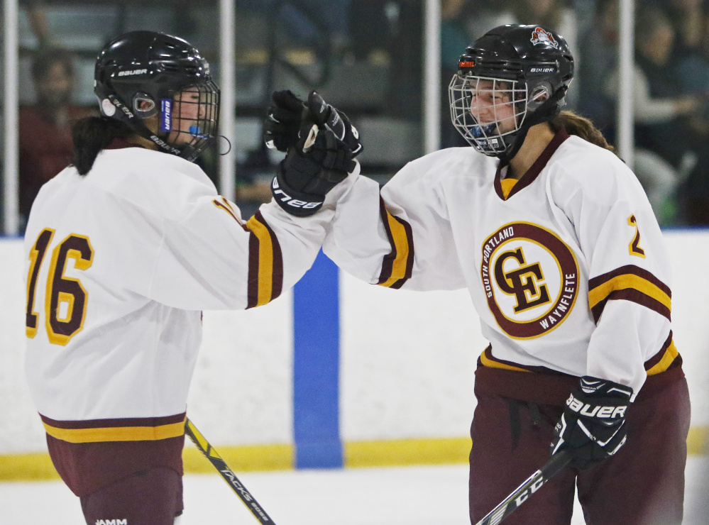 Koto Yamada, left, and Nicoletta Coupe celebrate Coupe's goal in the second period Saturday that helped Cape Elizabeth to a 12-2 victory against Gorham in a girls' hockey opener at Troubh Arena.