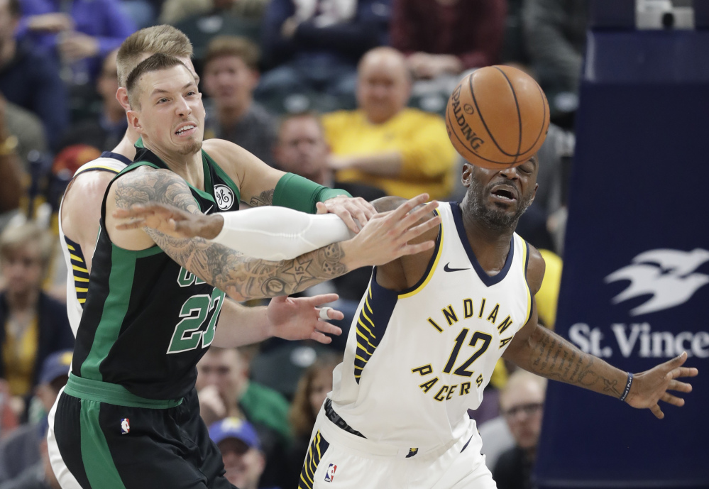 Daniel Theis, left, of the Boston Celtics battles with Damien Wilkins of the Indiana Pacers for a loose ball during the first half of Saturday;s game in Indianapolis. The Celtics held a 37-16 scoring advantage in the third period and went on to a 108-98 win.