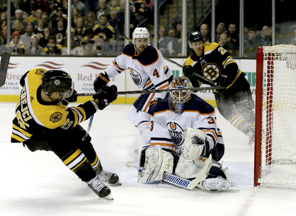 Boston Bruins center David Krejci scores against Edmonton Oilers goaltender Cam Talbot, tying Sunday's game in Boston at 2-2 with 4:29 left in the second period. The Oilers scored twice in the third period to win 4-2.
