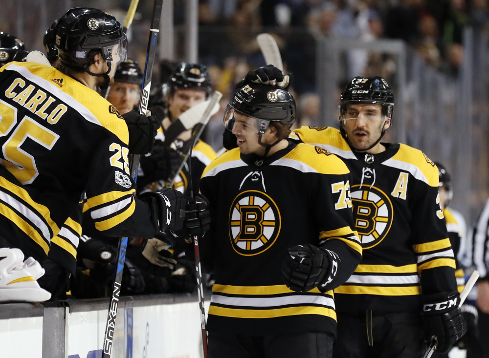 Boston's Charlie McAvoy is congratulated by Patrice Bergeron and Brandon Carlo, 25, after scoring in the first period Wednesday night in Boston against the Tampa Bay Lightning.