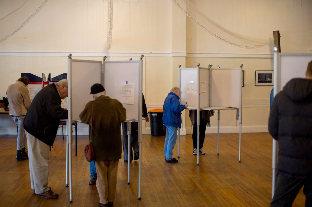 Voters fill out their ballots Tuesday at the Woodfords Club polling place in Portland's District 3. Voters in the off-peninsula district rejected the zoning and rent proposals on the city ballot by wide margins.