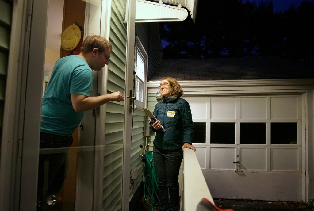 Hillary Barter, a volunteer with Mainers for Health Care, talks with a Westbrook resident Tuesday evening while canvassing for votes for the Medicaid expansion referendum on the statewide ballot.