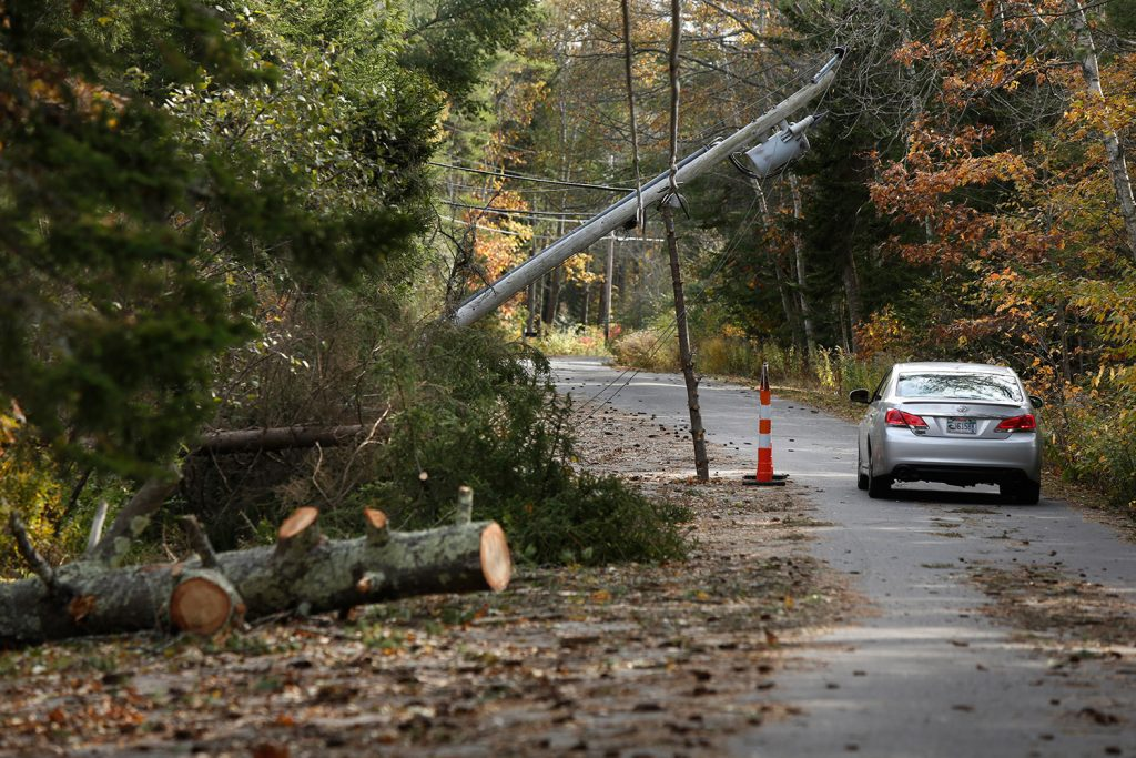 A motorist drives under a falled utility pole propped up by a pine tree limb on High Head Road in Harpswell on Wednesday.