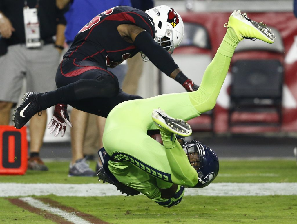 Seattle Seahawks wide receiver Paul Richardson makes the catch as Arizona Cardinals safety Budda Baker, left, defends in the first half Thursday night in Glendale, Ariz.