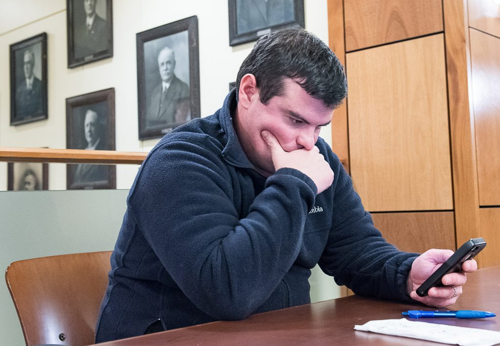 Auburn mayoral candidate Adam Lee checks his email as he keeps a running tally on a napkin on the second floor of Auburn Hall on Tuesday night as election results start to come in.
