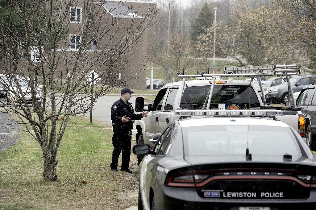 Community Resource Officer Charlie Weaver of the Lewiston Police Department talks with a motorist about the lockdown at Lewiston High School on Monday.