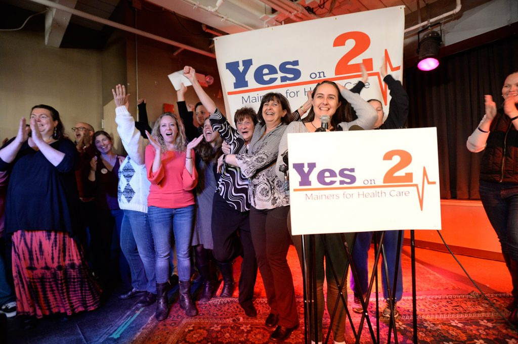 Jennie Pirkl, campaign manager for Mainers for Health Care, at the microphone, is joined by other supporters of state ballot Question 2, the expansion of Medicaid in Maine, as they celebrate their apparent victory at the polls on Election Day at Bayside Bowl in Portland.