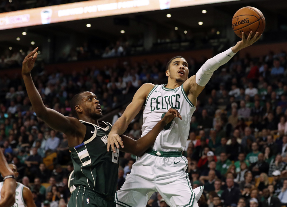 The Celtics' Jayson Tatum goes to the basket past the Bucks' Khris Middleton in the second quarter of Monday night's home win by the Celtics.