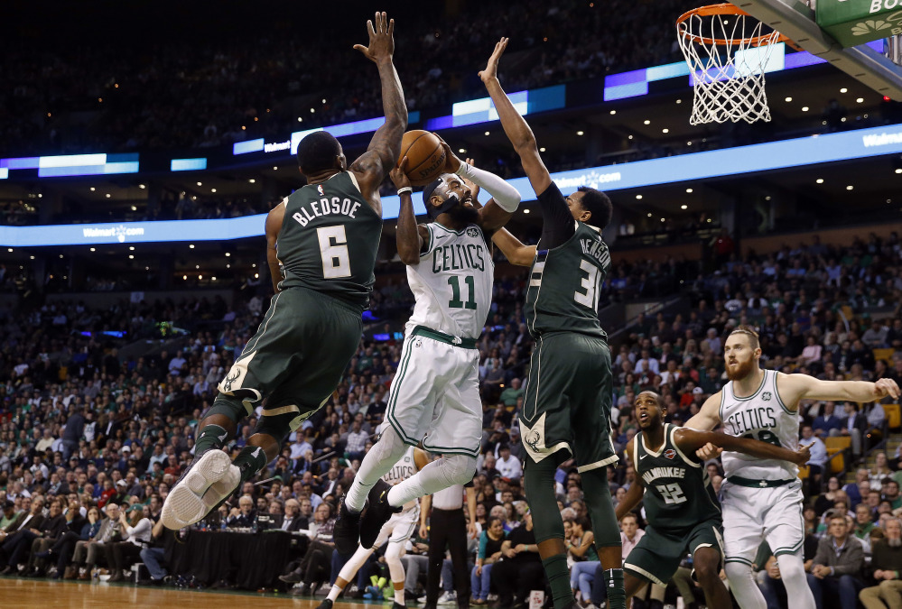 Boston's Kyrie Irving goes to the basket between Milwaukee's Eric Bledsoe (6) and John Henson in the second quarter. Irving led the Celtics with 32 points.