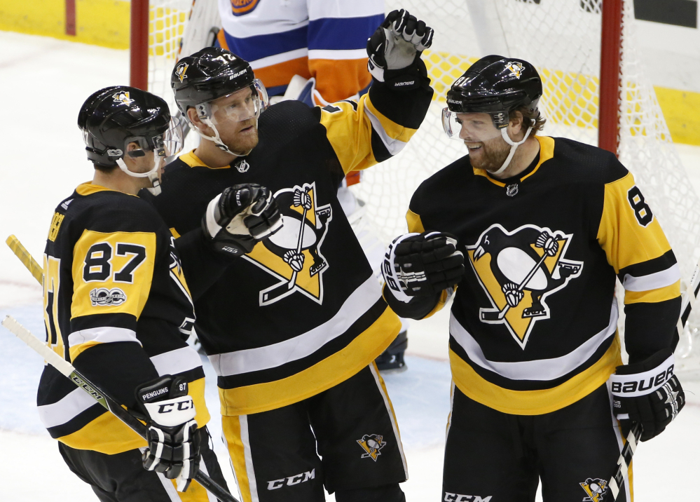 Pittsburgh's Phil Kessel celebrates his goal with Sidney Crosby, 87, and Patric Hornqvist, 72, in the third period Thursday night against the Islanders in Pittsburgh.