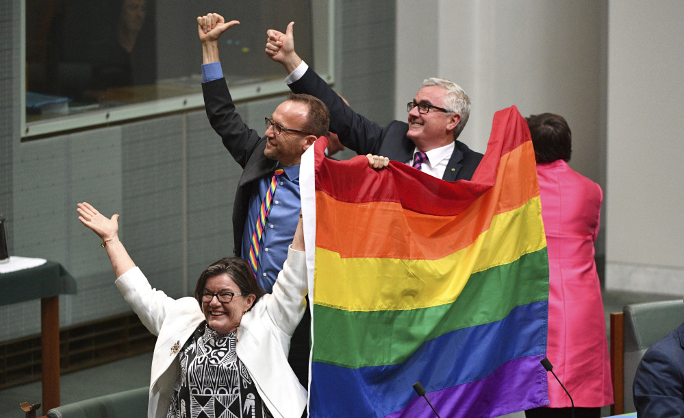 Parliament members celebrate the nearly unanimous passing of the Marriage Amendment Bill in Canberra, Australia.