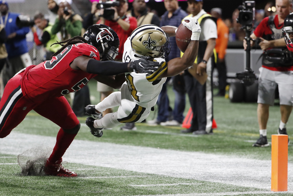 New Orleans wide receiver Tommylee Lewis dives into the end zone for a touchdown against Atlanta Falcons outside linebacker De'Vondre Campbell in the first half Thursday night in Atlanta.