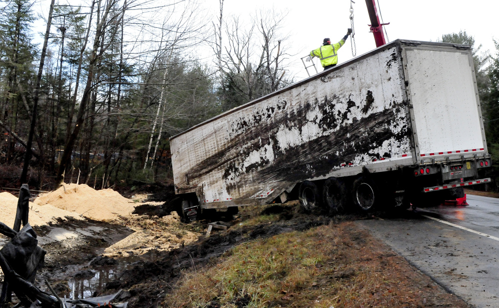 Tow truck operators work on connecting cables to a tractor-trailer carrying sawdust that overturned early Wednesday morning on Route 150 in Athens.