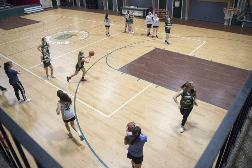 The Temple Academy girls basketball team practices at Temple Academy in Waterville on Friday. The team includes students from nine countries, including the United States, and is headed for the tournament with a record of 14-4.