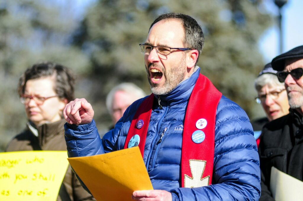 The Rev. Allen Ewing-Merrill speaks during a rally Wednesday in the plaza between the Burton M. Cross State Office Building and Maine State House in Augusta.
