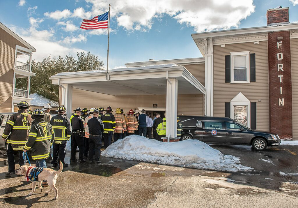 Firefighters in turnout gear arrive in Lewiston to escort the body of  Oxford Fire Chief Gary Sacco into the Fortin funeral home.