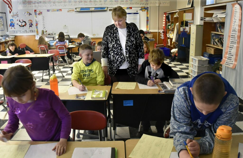 Quimby Middle School teacher Cathy Foran works with her fourth-grade students Wednesday at the school in Bingham. District voters have decided to close the school at the end of the school year.
