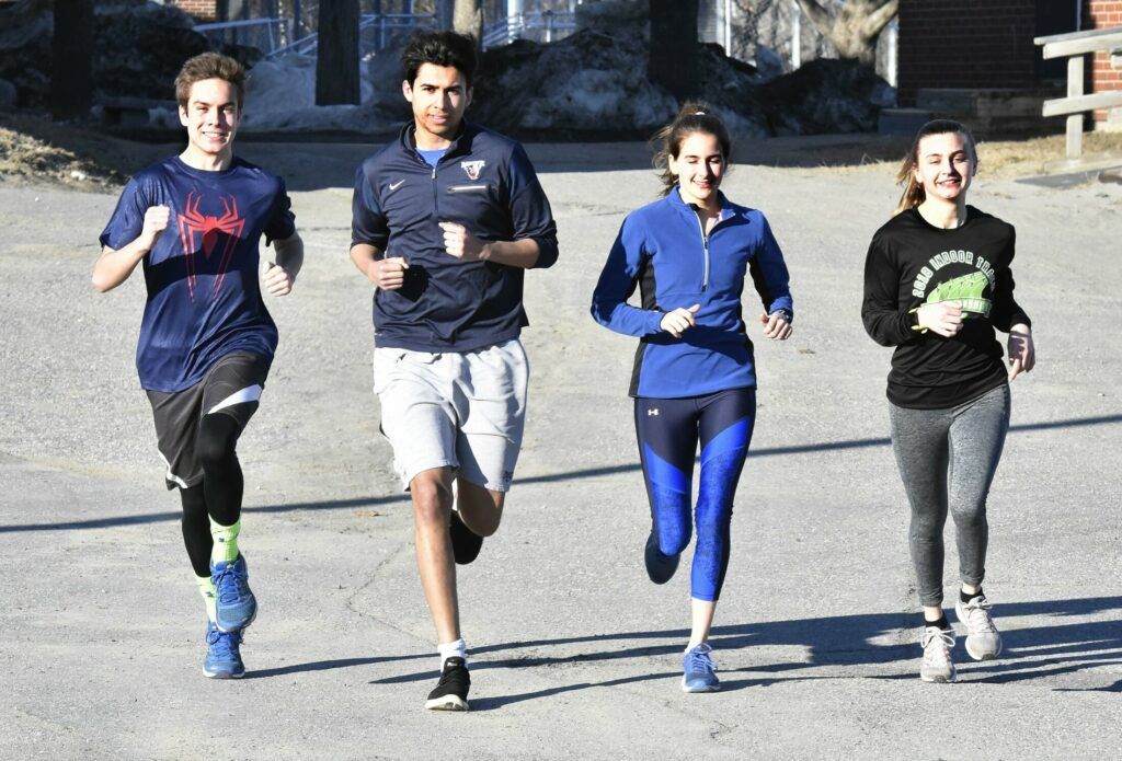 Messalonskee High School runners, from left, Hunter Smart, Sami Benayad, Sarah Kohl and Peyton Arbour run in Oakland on the first day of practice Monday.