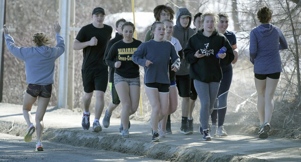 Members of the Maranacook track and field teams head out for a run during a preseason practice in Readfield.