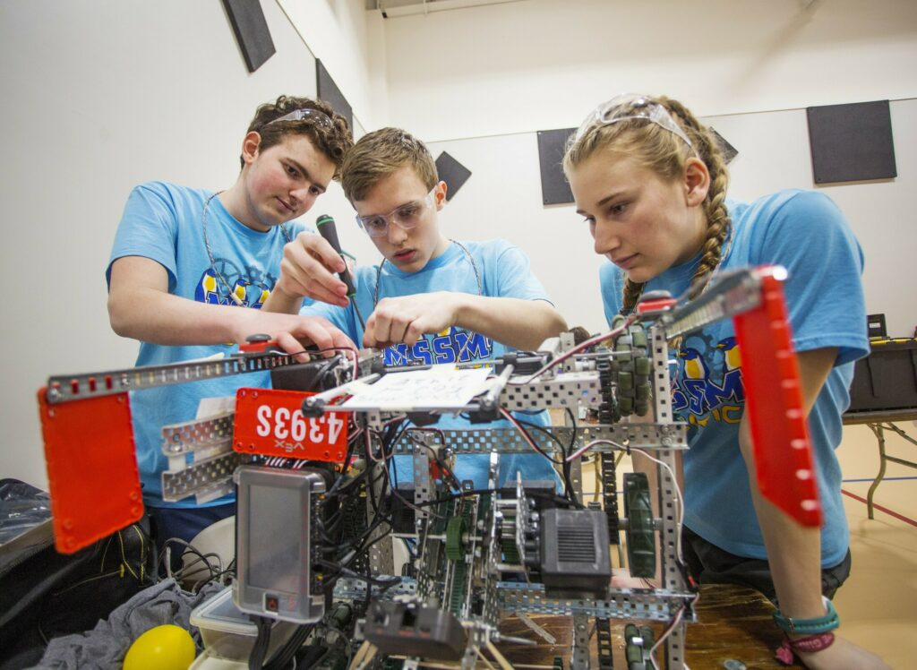 Maine School of Science and Mathematics teammates Wesley Chalmers, left, a sophomore, Chandler Pike, a freshman, and Madison McCarthy, a sophomore, make repairs to their robot between matches in the Maine VEX State Robotics Championship on Feb. 23 in South Portland. Their school has been ranked second in the nation by U.S. News and World Report.