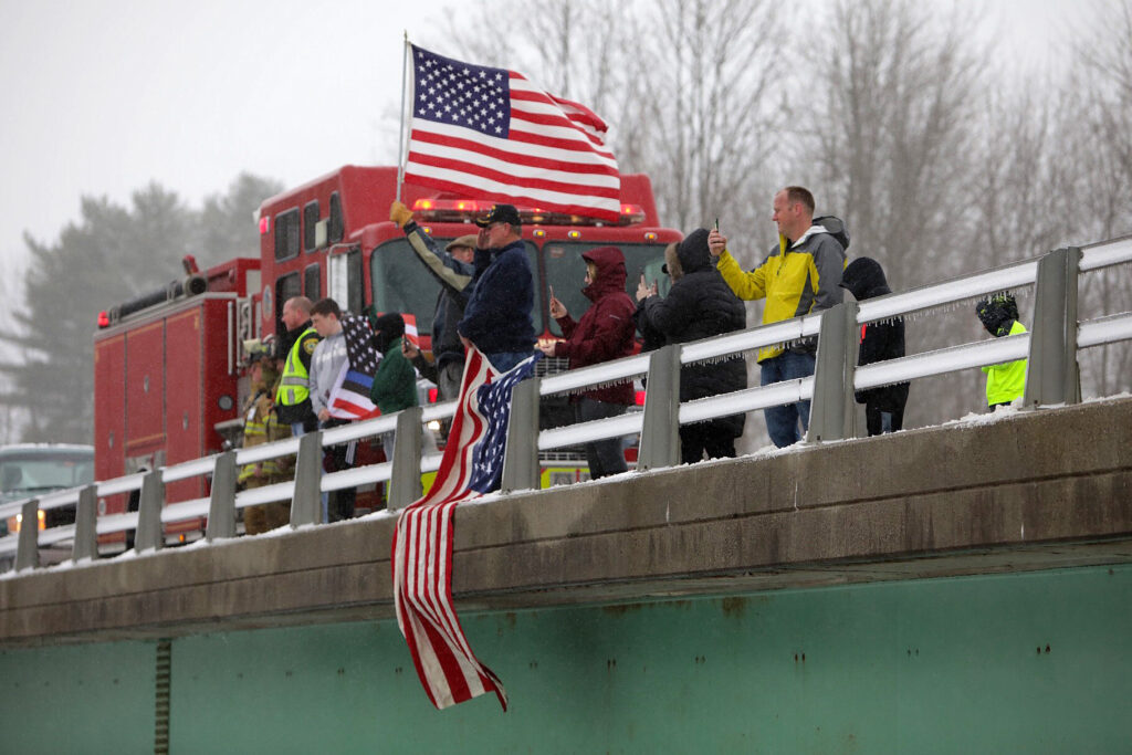 Representatives of the Richmond Fire Department and the Sagadahoc County Sheriff's Office, local veterans, and residents stand on an Interstate 295 overpass in Richmond on Monday to honor Maine State Police detective Benjamin Campbell as the procession with his body makes its way to Portland for Tuesday's funeral service.