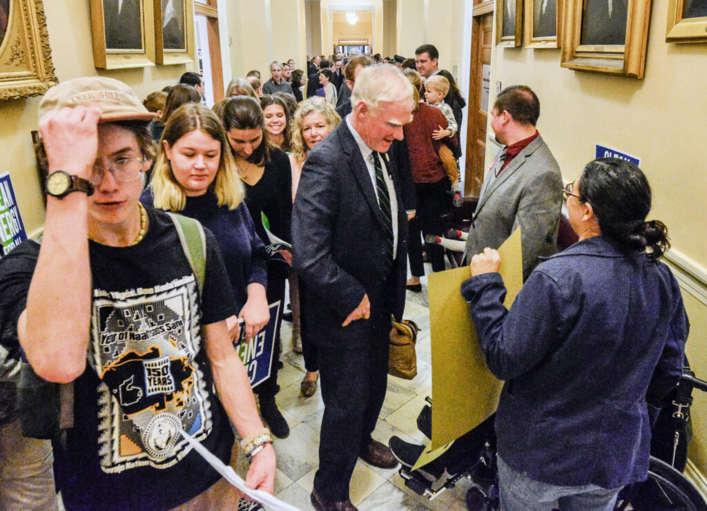 Sen. Brownie Carson, D-Harpswell, walks through the crowded hallway into the Senate chamber on Tuesday. State House hallways were crowded with people holding signs for and against a bill to remove religious and philosophical exemptions for public school vaccination requirements.