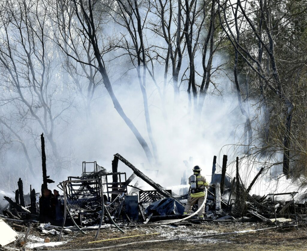 A firefighter sprays water on the burning remains of a barn at 658 Webber Pond Road in Vassalboro on Sunday.