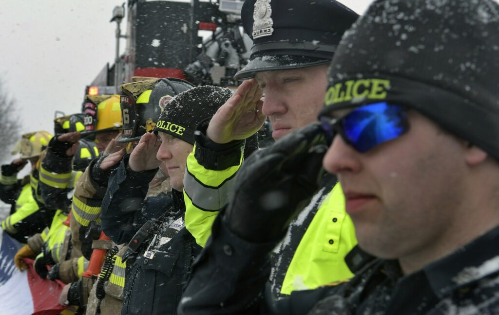 Monday's snow didn't deter Augusta police and firefighters from saluting the remains of Maine State Police Det. Benjamin Campbell, which were being escorted through Augusta to Portland for his funeral on Tuesday. Firefighters unfurled a 12-foot-long American flag on the side of Belgrade Road overpass on Interstate 95 as troopers passed by.