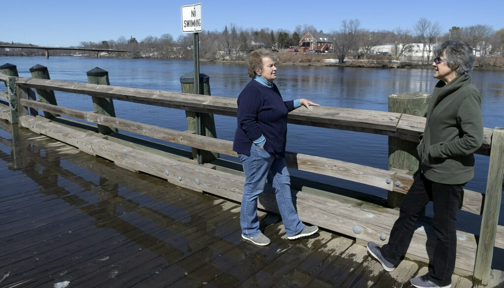 Liane Slade, left, and Merrilee McMillin chat Thursday on the waterfront along the Kennebec River in Gardiner. Rain and warm weather are in the forecast for this weekend, raising the potential for flooding at the start of next week.