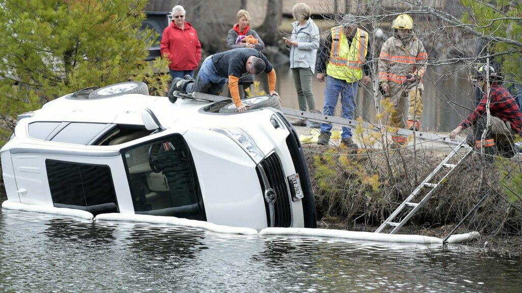 A Litchfield firefighter inspects a vehicle that overturned into Woodbury Pond on Monday in Litchfield.