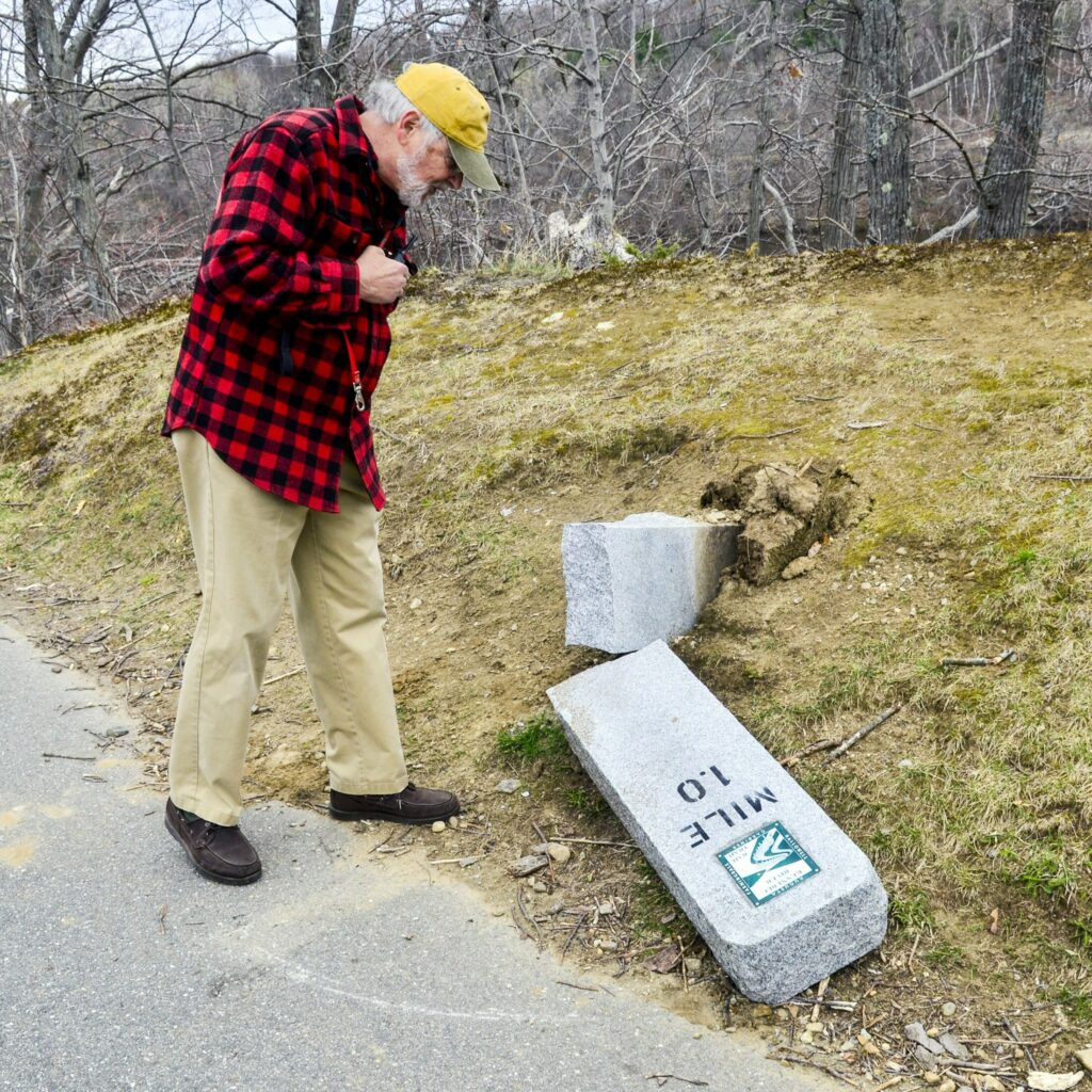 Paul Daiute looks at the tipped over one mile marker of the Kennebec River Rail Trail on Tuesday in Augusta.
