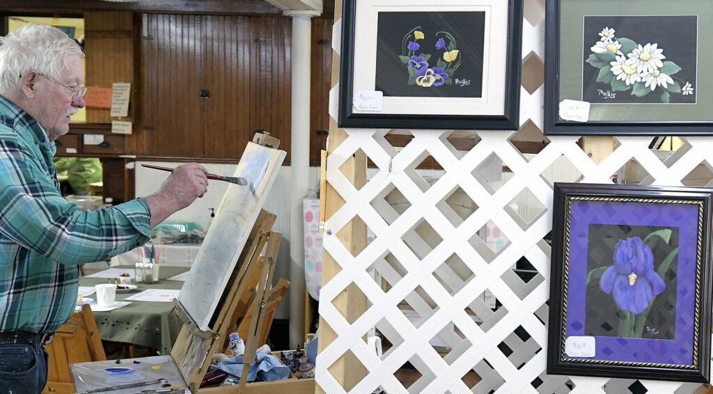 Jim Pecker paints with acrylics Sunday during an art show at the grange hall in Richmond.