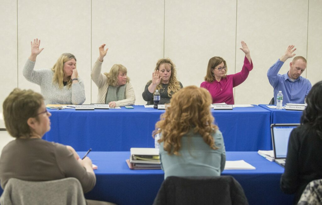 School Administrative District 49 board members — at rear from left, Katie Flood-Gerow, Kara Kugelmeyer, Katrina Dumont, Jenny Boyden and Shawn Knox — vote with six other board members to put out to bid a request for proposal for legal counsel during an April 11 school board meeting at Lawrence junior High School in Fairfield.
