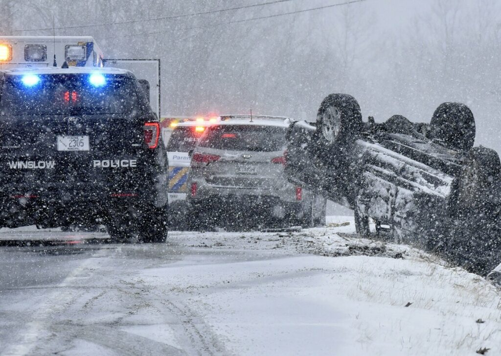 A vehicle rolled over on the snow-covered Route 137, also called China Road, in Winslow on Monday.